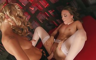 A duo of babes is fucking with a strap on in the dungeon